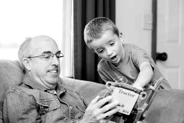 Grandfather and grandson with a book about tractors. Image by ambermb from Pixabay.