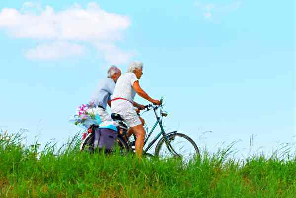 Older couple cycling with shopping in rural landscape. Image by Mabel Amber from Pixabay